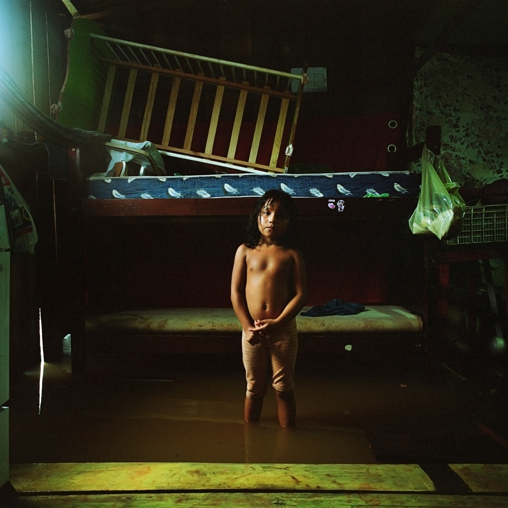 March 8, 2014. A girl stands in her flooded house in Invasao dos Padres, a neighbourhood in Altamira that will be permanently flooded by the Belo Monte Dam. The dam is expected to displace between 20 and 40 thousands people.