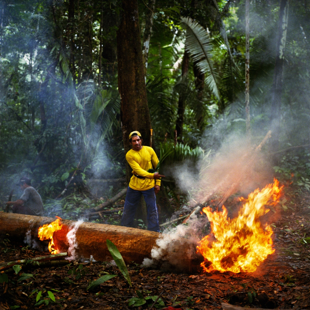 April 8, 2014. Neto fans the flames while building a canoe in the Riozinho do Anfrisio Extractavist Reserve in the Xingu Basin. Extractavists have lived in the forests for generations descending from the rubber tappers that once fed Brazils rubber boom. Today they live along the river banks with an economy based on harvesting sustainable natural products such as latex, nuts, and oils. As this communtiy is a few days away by boat from the Belo Monte Dam, the direct and indirect impacts are not fully understood.