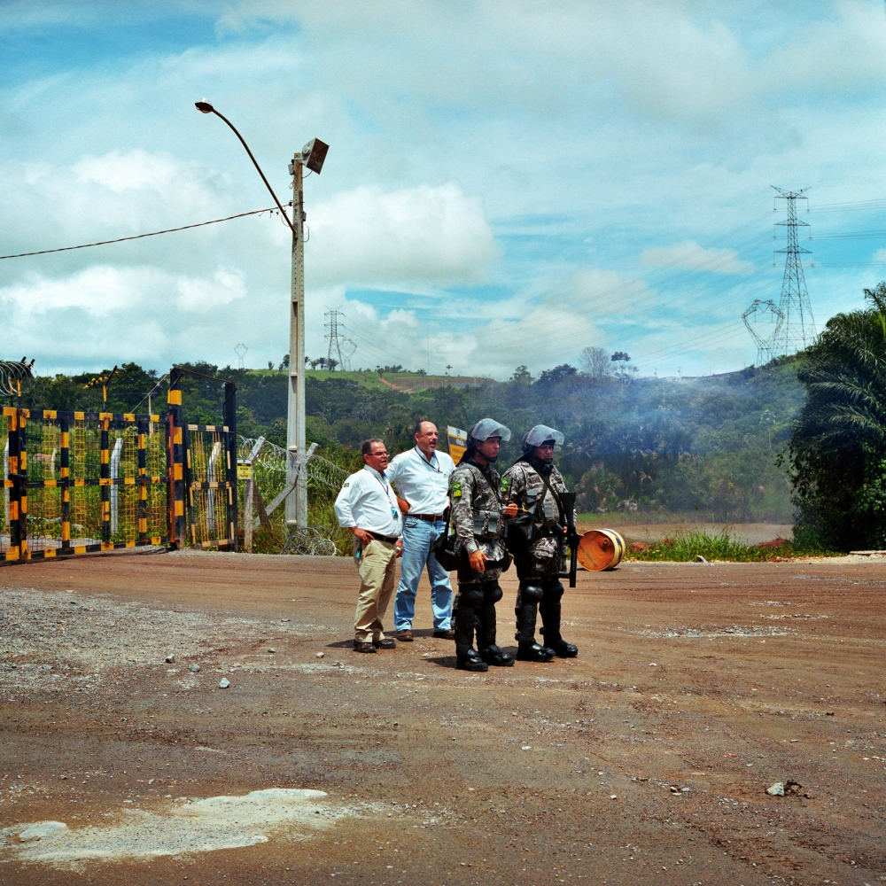 March 18, 2014. Executives from Norte Energia, the consortium building the Belo Monte Dam, stand behind National Force soldiers pior to negotiating with a group of fisherman that have occupied the entrance to the Belo Monte construction site.