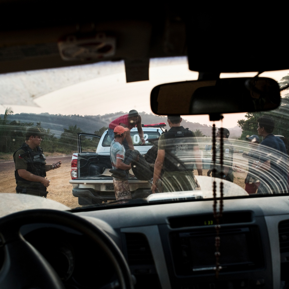 "November 29, 2014. An artisan gold miner or ""garimpeiro"" is loaded in to the back of a police truck after he died in an accident while working along the Tapajos River in Para, Brazil. Illegal and artisan gold mining is one of the main industries along many of the rivers in the Amazon. Many of the miners worry that once the hydroelectric dams are completed, international mining companies will proliferate in the area and put locals out of work. While artisan gold mining is damaging to the environment, industrial scale mines pose a much greater threat, and will syphon profits outside of the local economies."