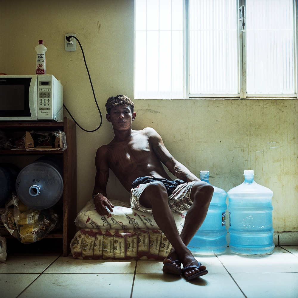 NOVEMBER 26, 2014. A member of the Munduruku indigenous tribe sits on bags of sugar and rice during an occupation of the FUNAI offices (Brazil's National Indian Foundation) in Itaituba. The occupation was in protest to the fact that FUNAI has refused to publish documents that would officially recognize Munduruku traditional territory. If recognized, flooding of the territory by new hydroelectric development would be illegal under Brazilian Law.