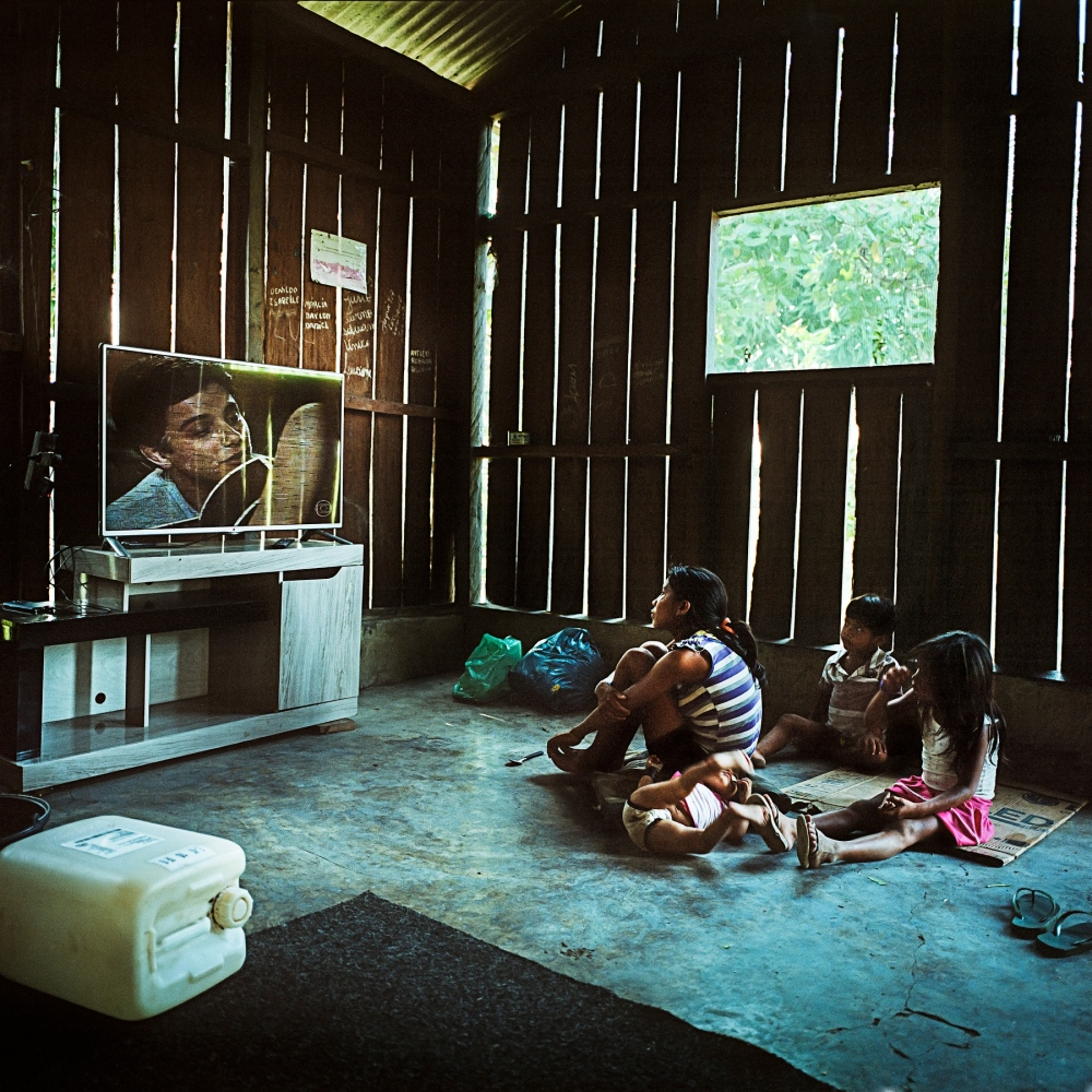 December 11, 2014.  A Munduruku family watch Brazilian Soap Operas  in the village of Sawre Muybu. Although living completely off the land their villages have generators, fridges and televisions often provided to them by government and industry hoping to win their support for the proposed dams.