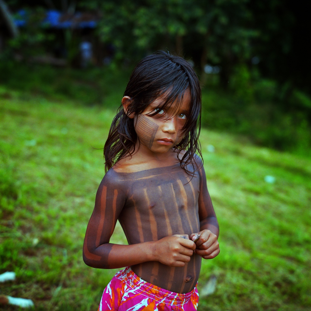 "February 20, 2014. A child from the Xikrin village of ""Pot crô"" stands on the banks of the Rio Bacaja, its name meaning ""the water that runs in river is the same as the blood that flows through our veins."" The Xikrin are part of the Kyapo warrior tribe that have strongly resisted the dam for decades and will be severely impacted by the dewatering of their river."