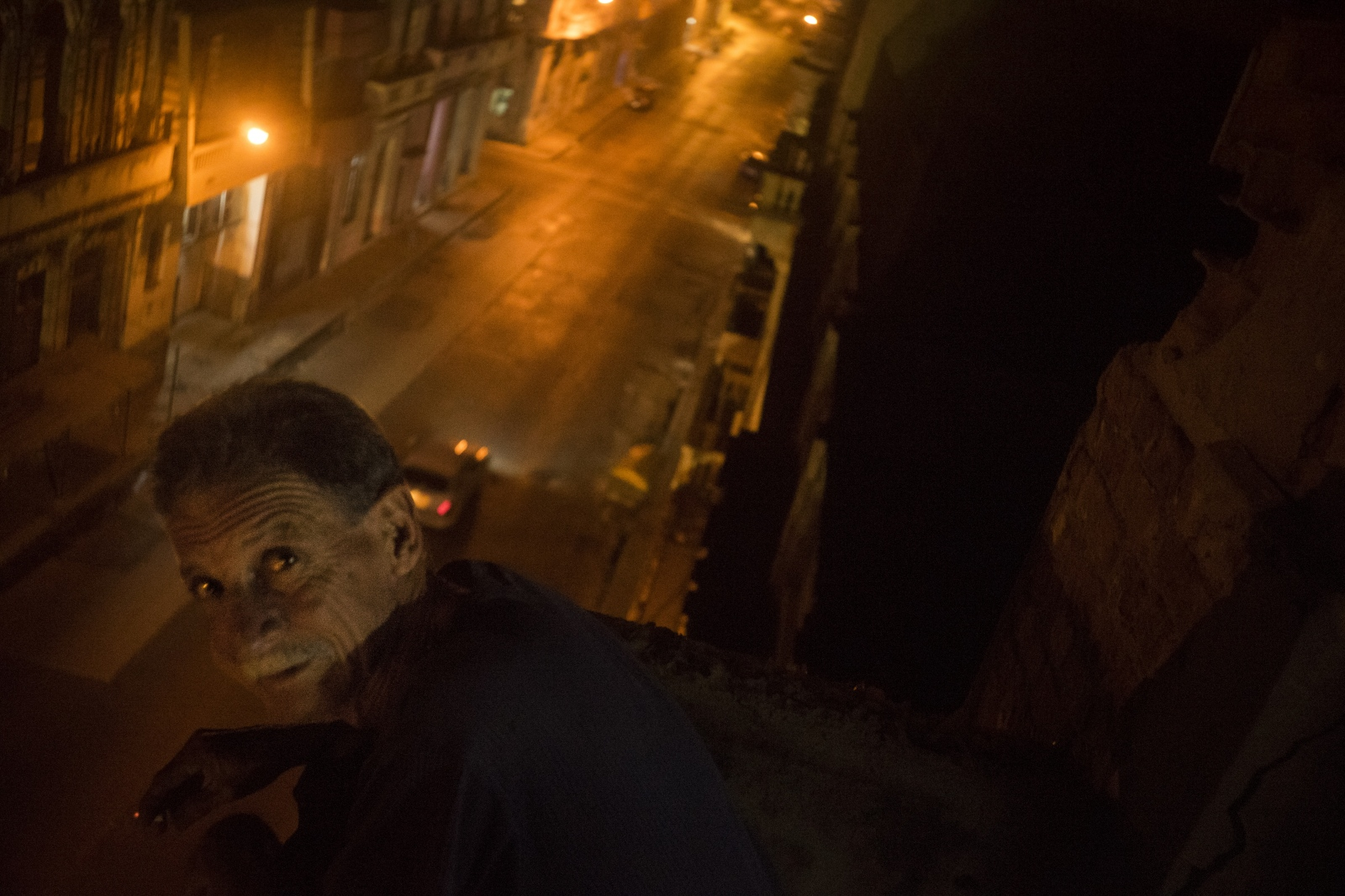 Carlos leans over his balcony while smoking a cigarette. He is an auto painter for a stateowned business.