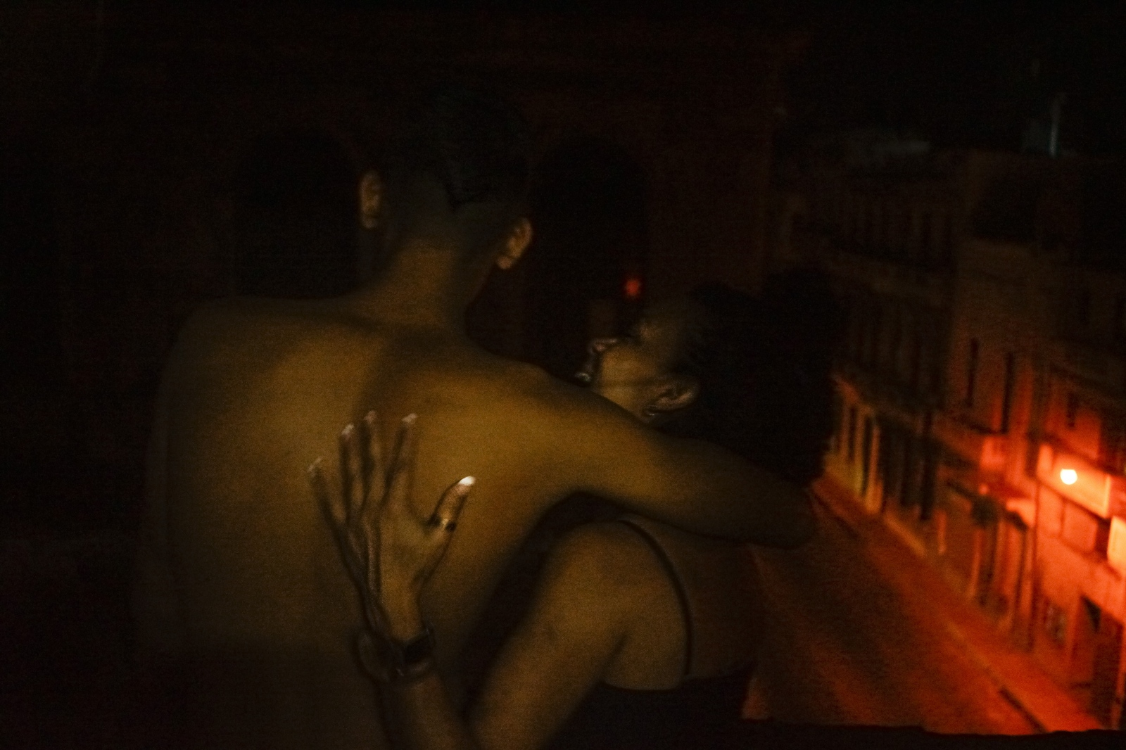 Ariam and Nidieska embrace on the balcony outside of their room.