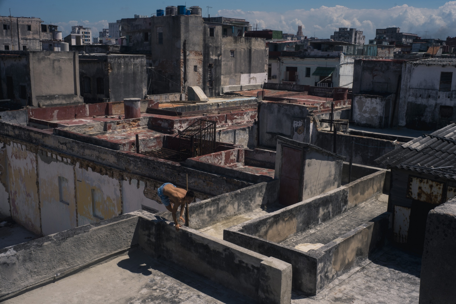 Ariam, a seventeen-year-old Cuban, runs across the roofs of his building complex. He lives in Central Havana, Cuba.