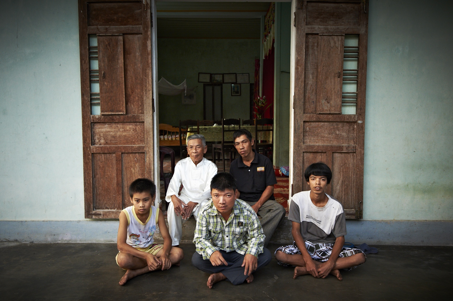 At a quick glance, they seem to be like any other families. But look closely and you will realize that there are three generations of victims of the Agent Orange in the family. The man dressed in white is the grandfather, Hoang Thang (Male, born in 1929), who got hit by the chemical in Hai Lang forest and to this day suffers from serious skin diseases and nervous system illnesses. His son, Hoang Van Danh (Male, born in 1977, top row on the right), has epilepsy with his right leg paralyzed, while his son, Hoang Anh Son (Male, born in 1983, eldest son's son), is mentally challenged with paralysis on his right leg and foot. Second son's son, Hoang Anh Duc (Male, born in 1994) is hearing impaired and mute. Lastly, third son's son, Hoang Quang Tuong (Male, born in 2002) has epilepsy. The pain and sufferings inflicted by the Agent Orange, most unfortunately, are passed on from one generation to the next. (Dec. 7, 2012)
