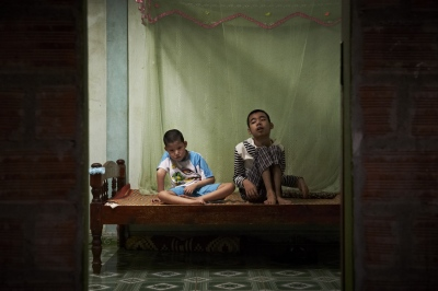 Hoang Van Binh (Male, age 12) and Hoang Van Nhat (Male, age 13) are cousins. Both have cerebral palsy, with inability to communicate and walk.  They rely on the wheel chairs that were sponsored by South Korean NGO to move around. Both their fathers seem normal, but have been working extensively in heavily contaminated areas, and have been consuming food products that were produced from those areas. (Dec. 5, 2012)