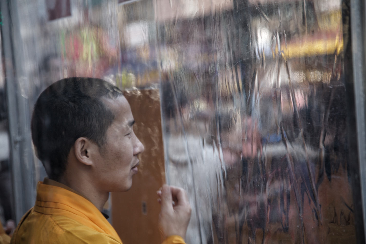 Buddhist monk surveys Canal Street on a rainy day.