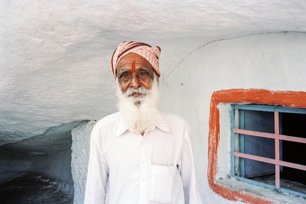 Temple Guide, Anegundi. Photographed outside a tiny temple in a cave amongst giant boulders.