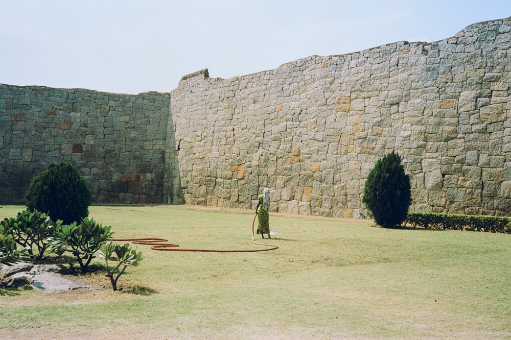 A woman waters the grass in the grounds of the Lakshmi Temple, Hampi.