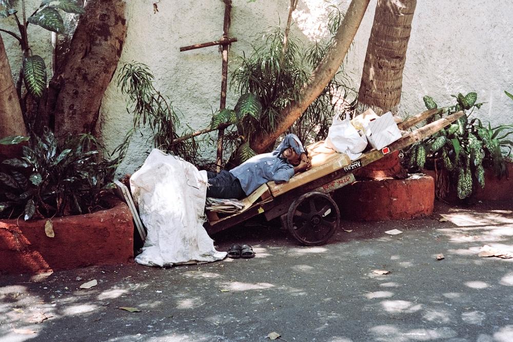 A man takes an afternoon nap on his cart.Colaba, Mumbai.