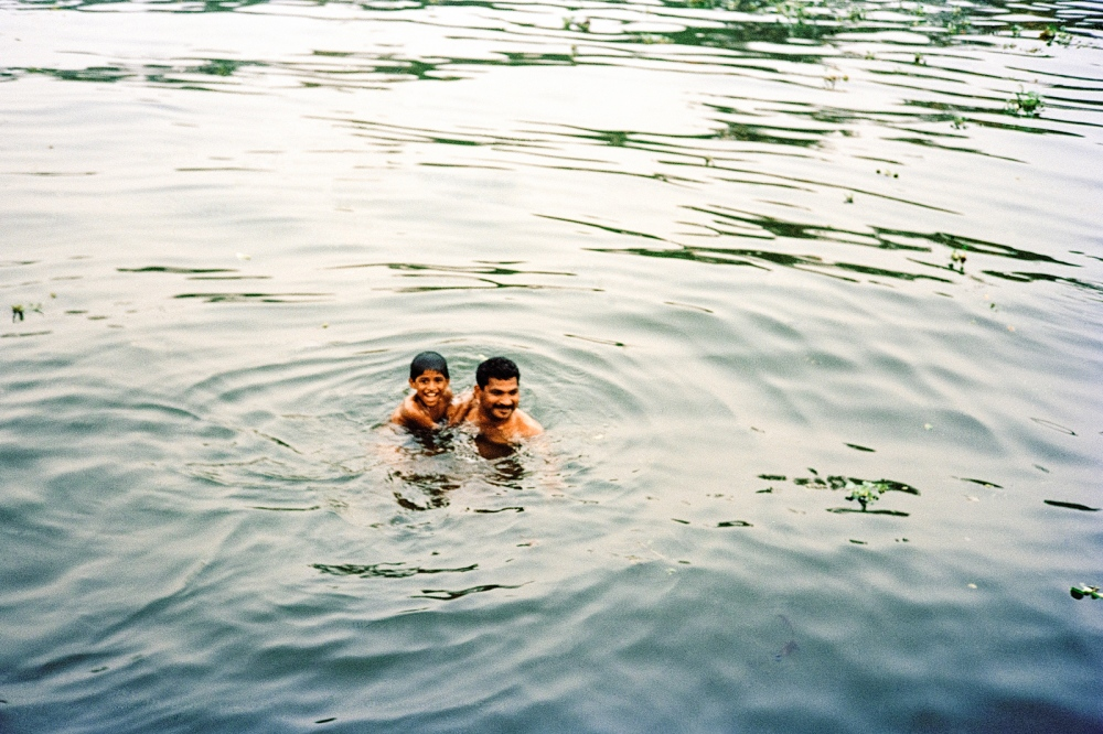 Father and son have an evening swim. Alleppey backwaters, Kerala.