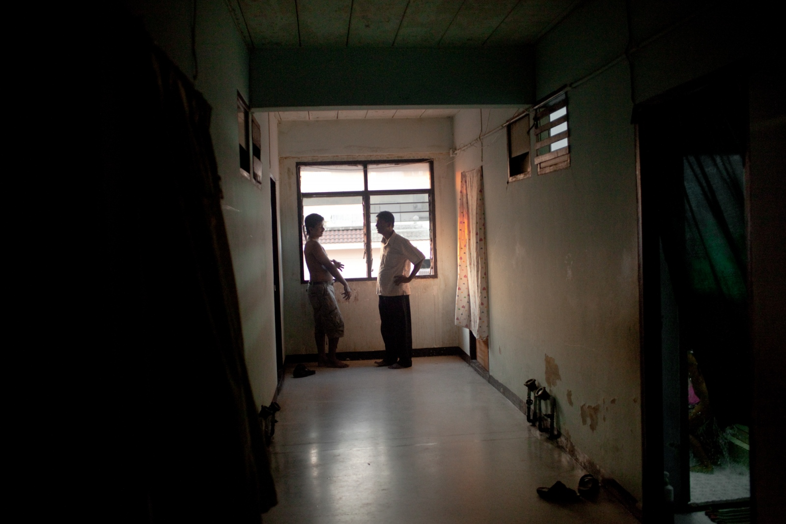 Two men from Sri Lanka stand near a window in the hallway of one of the main buildings, that house hundreds of asylum-seekers. Apr. 2015
