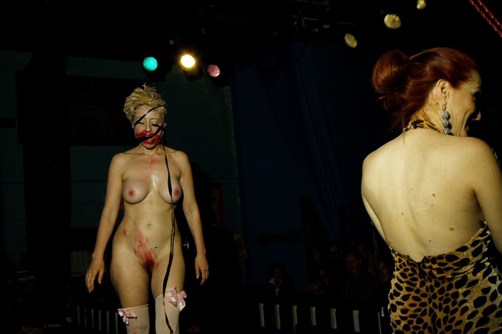 "Neo Burlesque performance artist Bunny Love exits the stage behind hostess Jo ""Boobs"" Weldon after a performance honoring analog technologies. The best Neo-Burlesque performers have gone far beyond traditional striptease deep into the realm of avant-garde performance art. After the performance, Love and Boobs took part in a panel discussion about burlesque's historical associations with sideshows."