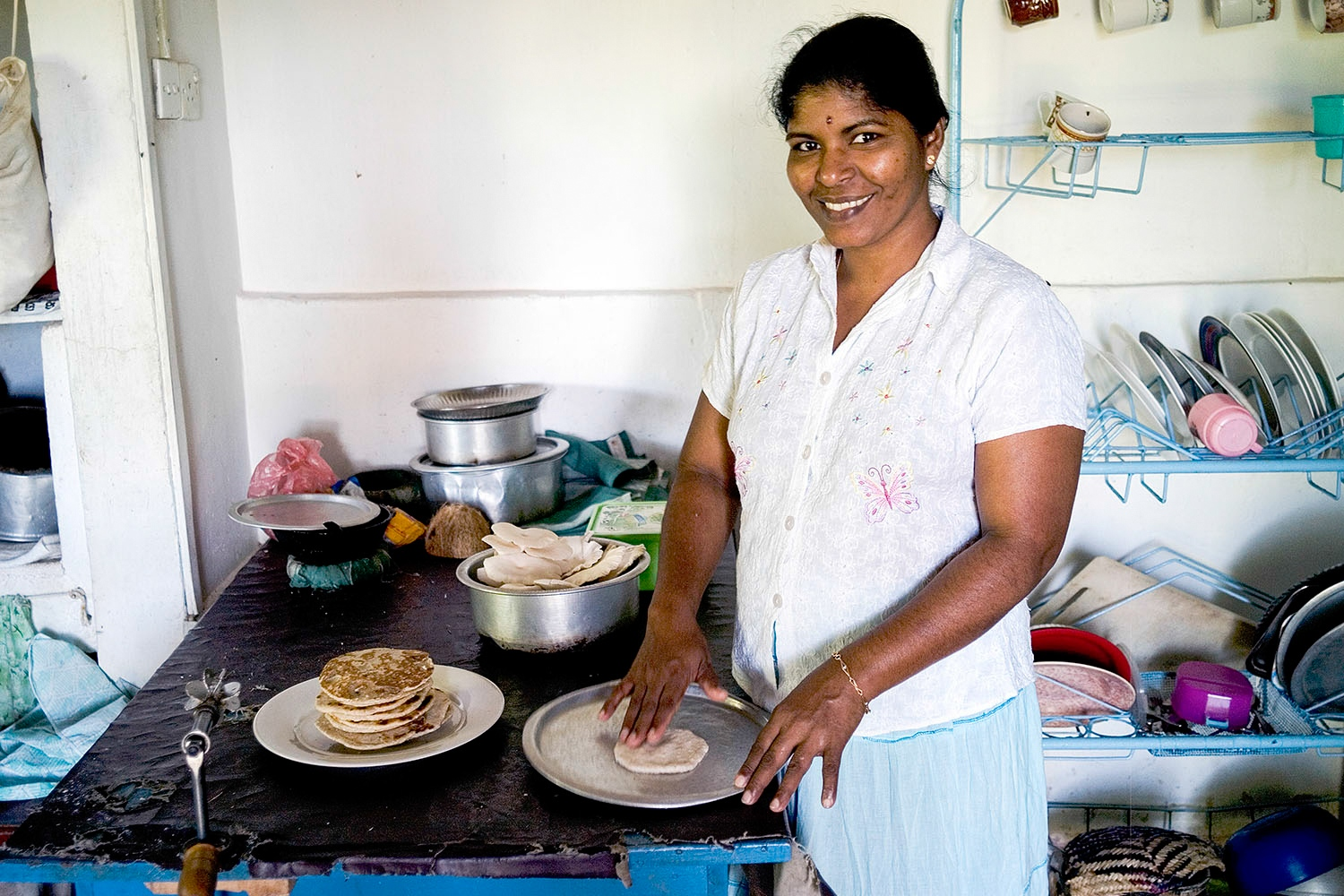 A volunteer makes roti in the community centre kitchen.