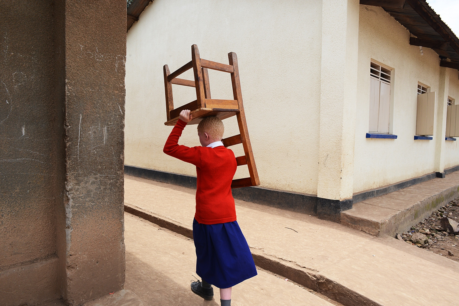 Natasha who was born with albinism carries a chair back to her classroom after recess. Albinism is a genetic condition that occurs in all racial and ethnic groups throughout the world but in Uganda and other African countries many born with the condition are discriminated against in ways that often lead to violence.