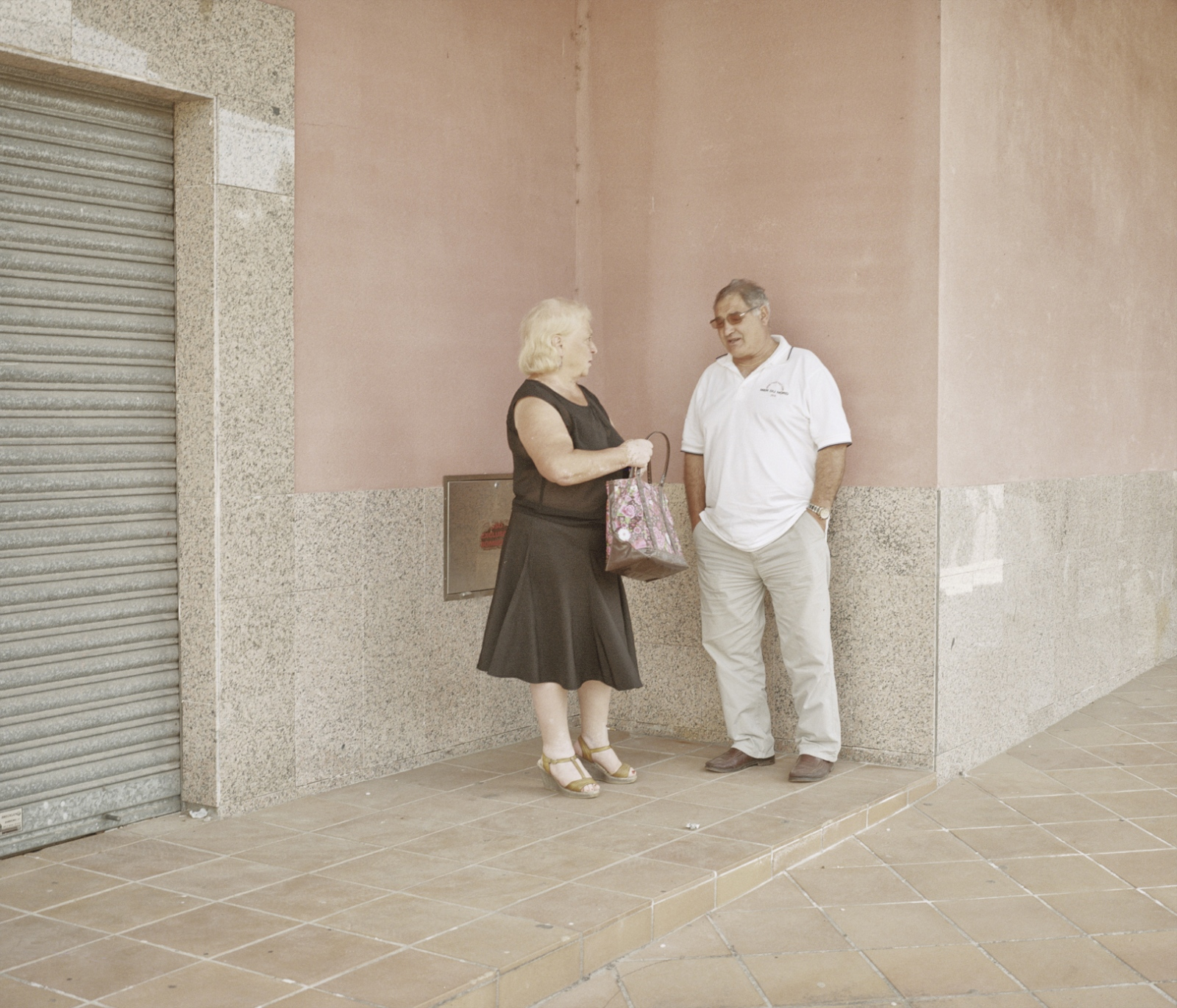 Spain, Goian. A local couple stand in front of a closed shop. During the economical crisis several local buisness closed for the lack of clients.