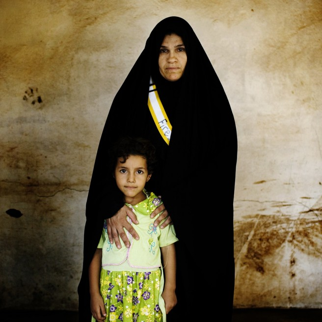 Fawzia Salah Abbas, 34, stands with her youngest child Tiba Moufez Abed, 5, who often accompanies Fawzia to work at checkpoints. Fawzia's oldest son died in a suicide bombing in December of 2007. Her husband was kidnapped February 19, 2006, & never seen again.