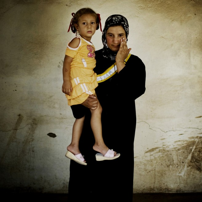 "Ridiya Mahmoud Haddam, 37, holds her only child Tabariq Waad Mi Zahem, 3. Her husband was kidnapped and beheaded in 2005 when her daughter was 2 months old. She has since struggled to provide for her family. ""You can see how poor I am, I am working in this risky job only for my daughter,"" she said."