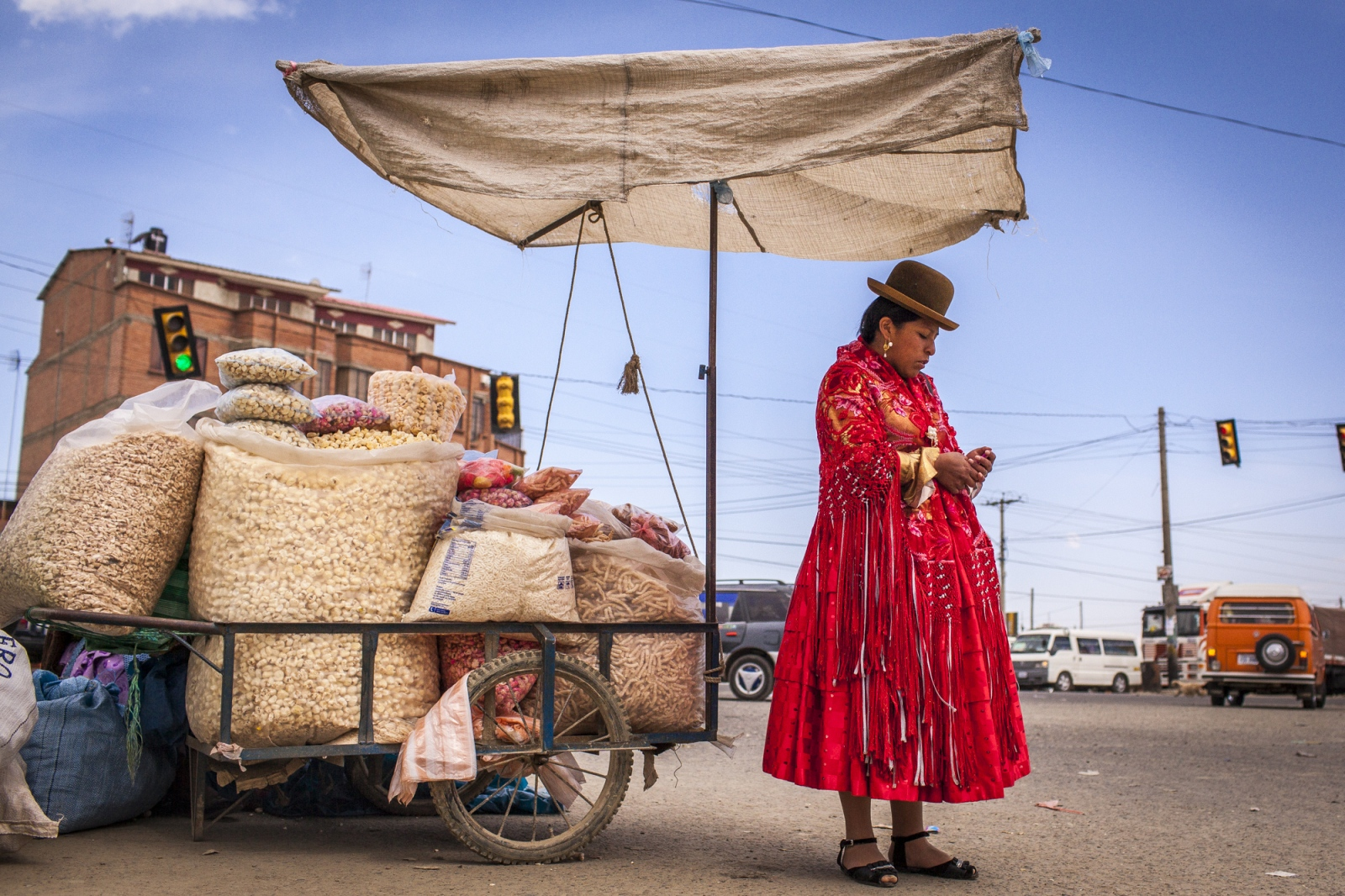 Reyna Torres, 22, waits at an intersection on the city of El Alto for the rest of the group so they can go together to a fight in Senkata. The wrestling cholitas fight every Sunday on the 12th October Complex in El Alto, but sometimes they do exhibition fights in other parts of La Paz and Bolivia to promote the sport.