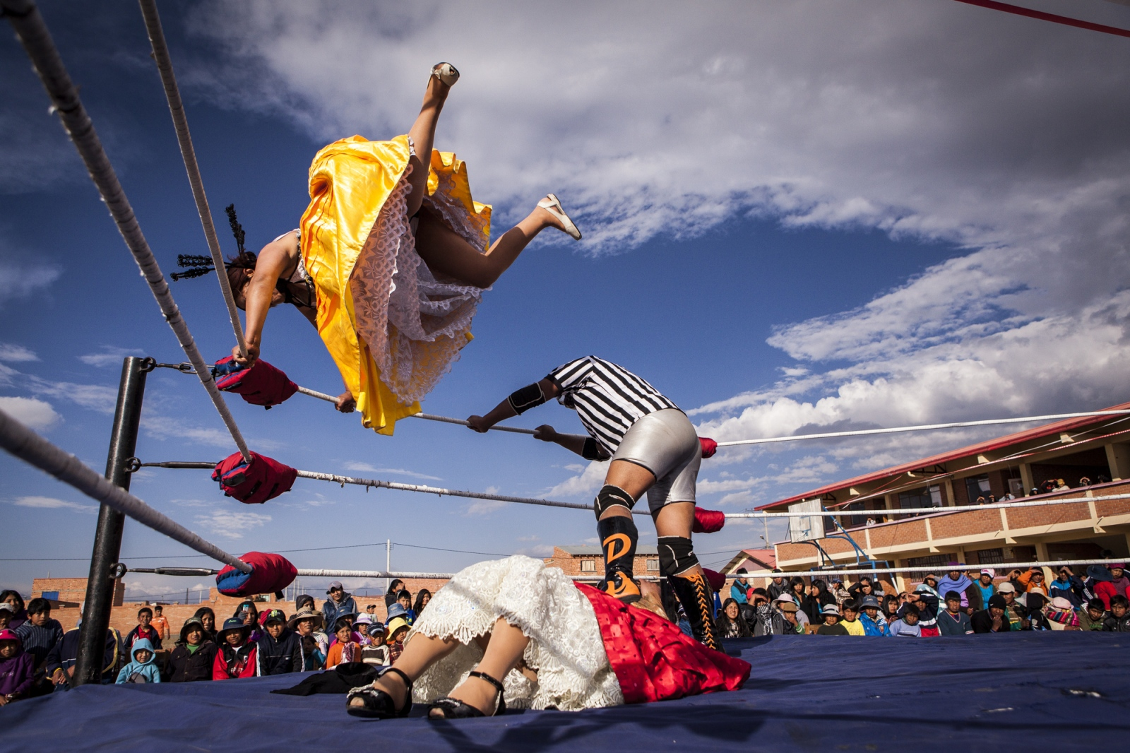Silvina La Poderosa jumps from a corner of the ring to land in her opponent, Reyna Torres, during exhibit fight in Senkata, El Alto.