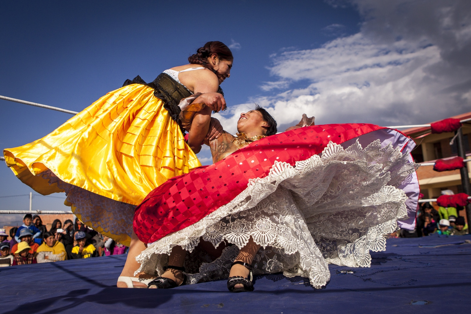 Reyna Torres grabs Silvina La Poderosa on a rotation movement during an exhibition fight in Senkata, El Alto. The Wrestling Cholitas fight every Sunday on the 12th October Complex in El Alto. At times they do exhibition fights in other parts of Bolivia to promote the sport.