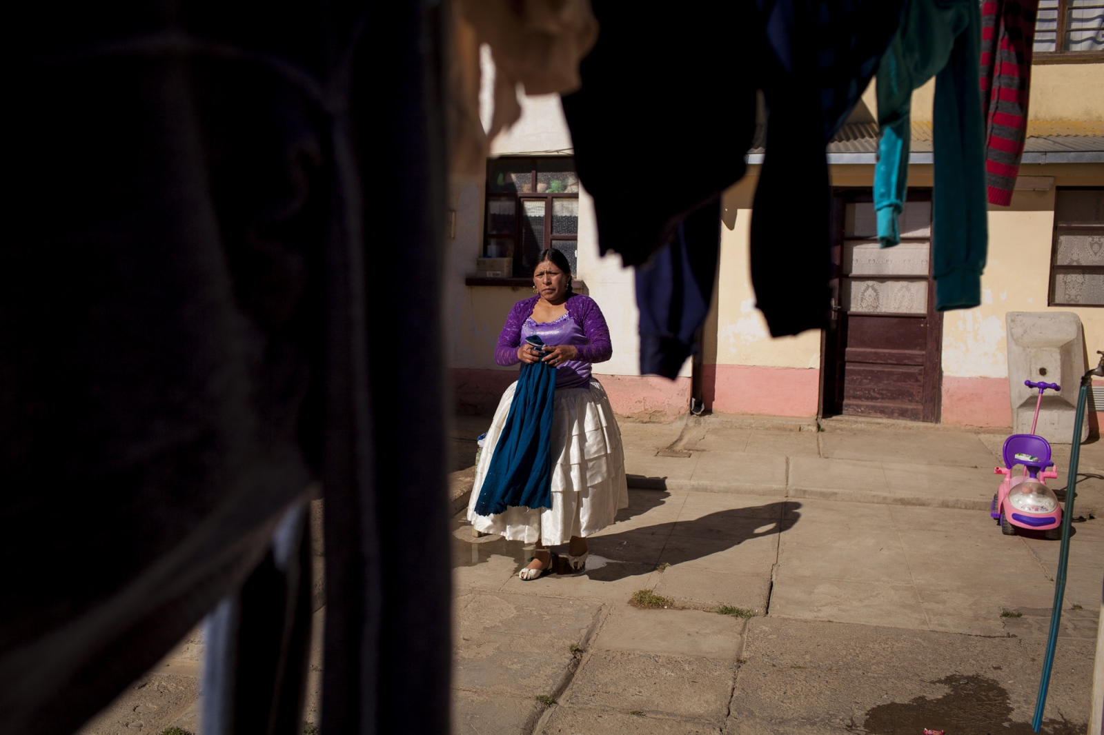 Reyna Torres, takes clothes to dry on a rope in her parent's home. When she is not fighting or involved in the organization of the fights she helps her mother in house duties. Reyna is one of the wrestling fighters part of the Cholitas Luchadoras group that fight every Sunday on the city of El Alto, Bolivia.