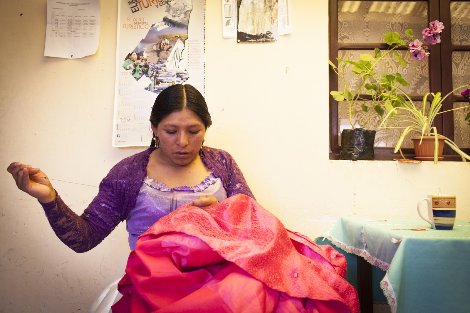 Reyna Torres sews a skirt that was damaged during a fight. Cholitas use their every day clothes  even on the ring. When she is not fighting or involved in the organization of the fights she works in her parents home. Reyna is one of the wrestling fighters part of the Cholitas Luchadoras group that fight every Sunday on the city of El Alto.