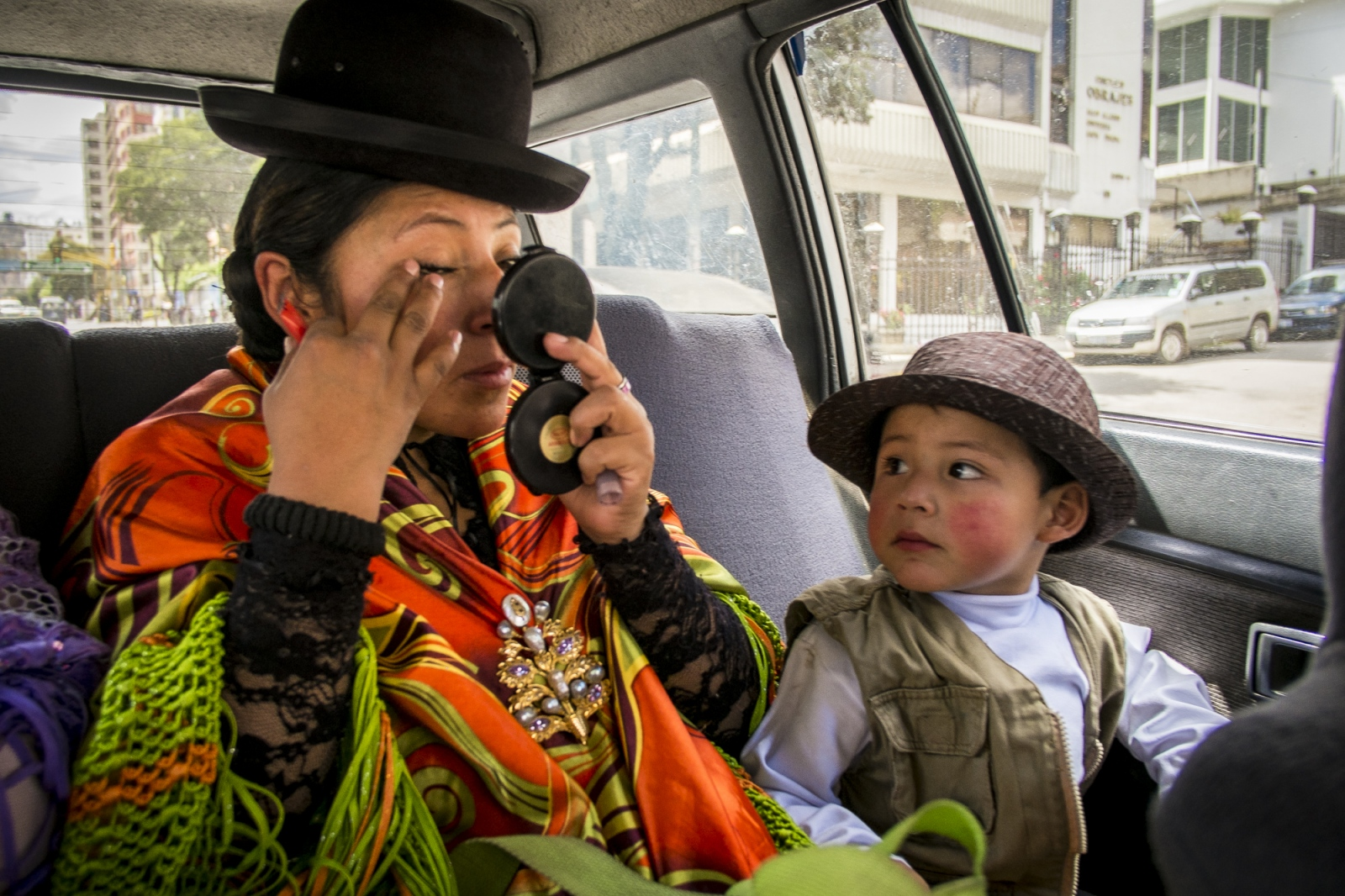 Mary Llanos Sanz, 31, best know as Juanita La Cariñosa (The Sweet One) the leader of the Wrestling Cholitas, puts make up on a taxi ride on the way to a fight while her little son looks at her.