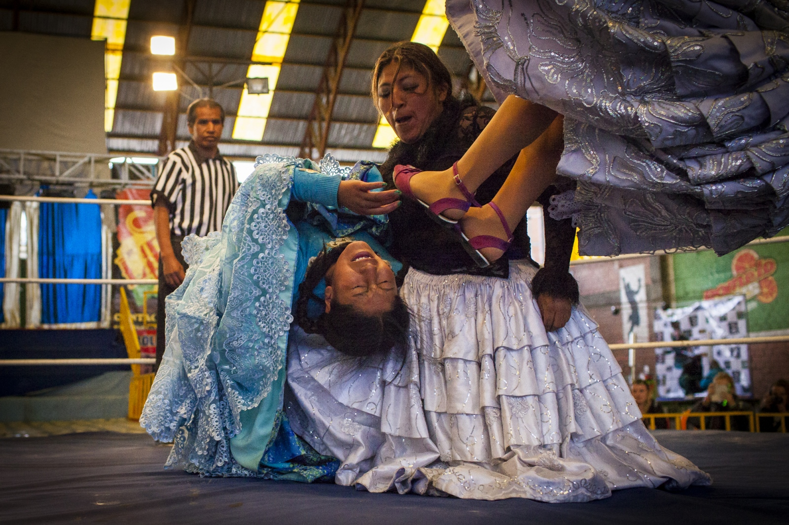 Juanita La Cariñosa and Simpática Sónia, 21, (Nice Sonia) punish Jennifer Dos Caras (Two Faces), 16, during a fight on the 12th October Sports Complex in El Alto. Sometimes fights are fought in pairs, being one team the bad and the other the good one. As in many other stories, most of the times the good side tends to win in the fight at the end after suffering a lot.