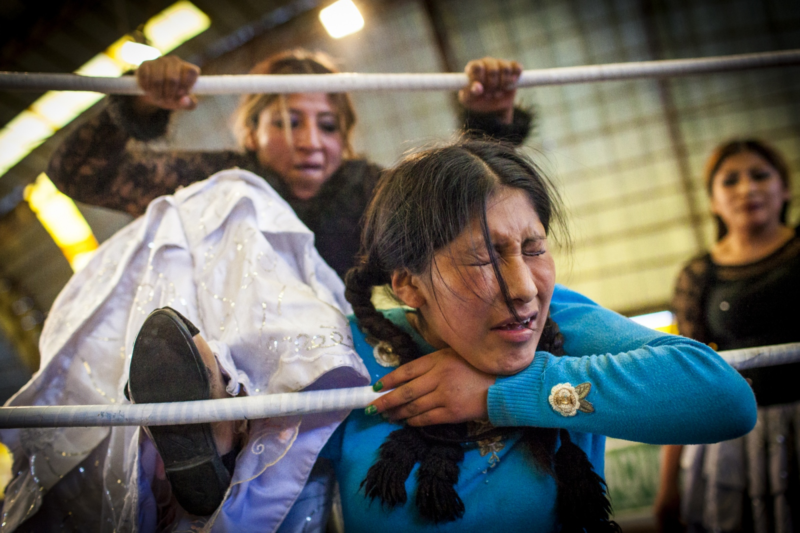 Juanita La Cariñosa punishes Jennifer Dos Caras (Two Faces), 16, on the ropes during a fight on the 12th October Sports Complex in El Alto. Sometimes fights are fought in pairs, being one team the bad  and the other the good one. As in many other stories, most of the times the good one tends to win the fight at the end after suffering a lot.