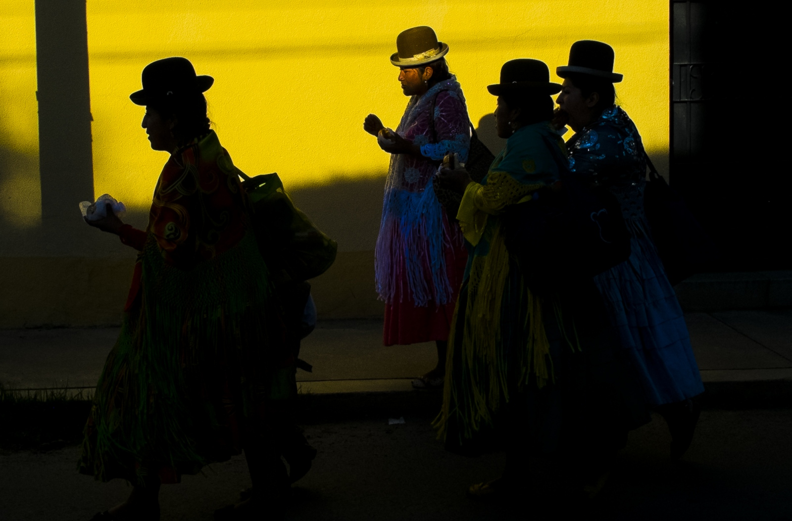 Cholitas walk on the street at sunset after an exhibition fight on the rich part of La Paz. The wrestling cholitas fight every Sunday on the 12th October Complex in El Alto, at times they do exhibition fights in other parts of La Paz and Bolivia to promote the sport.