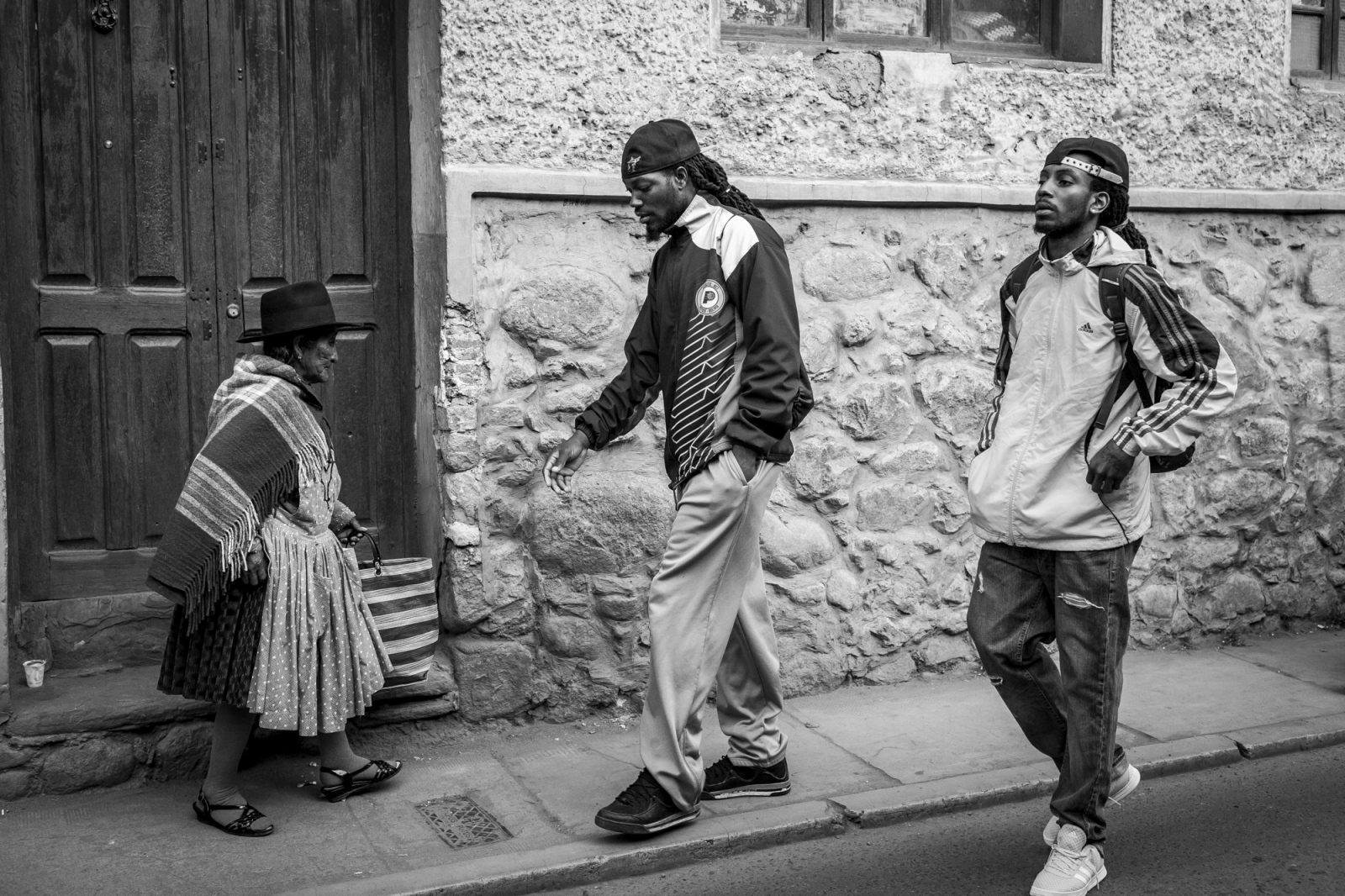 Travis Dupree and Domonick Steverson walk next to a Cholita on the streets of Potosí. American basketball players are looking for new markets to continue their careers and Bolivia recently has  been receiveing with open arms this influx of players.