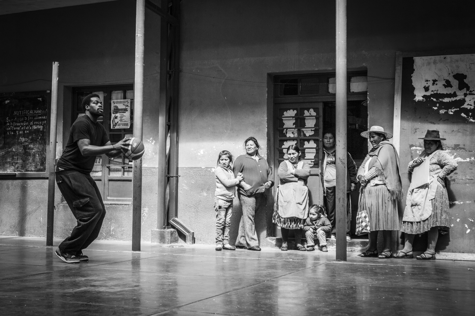 Cholitas look with curiosity to DeQuan Massey while he shoots for a three point during a free session at Sucre School in Potosí.