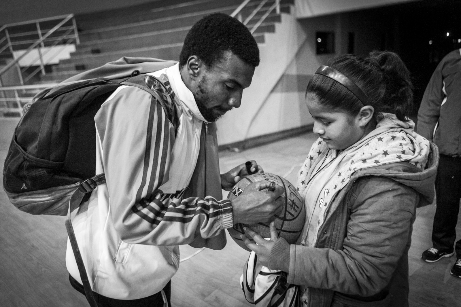 Tadavius Williams signs the ball of a fan after the game against Pichincha.