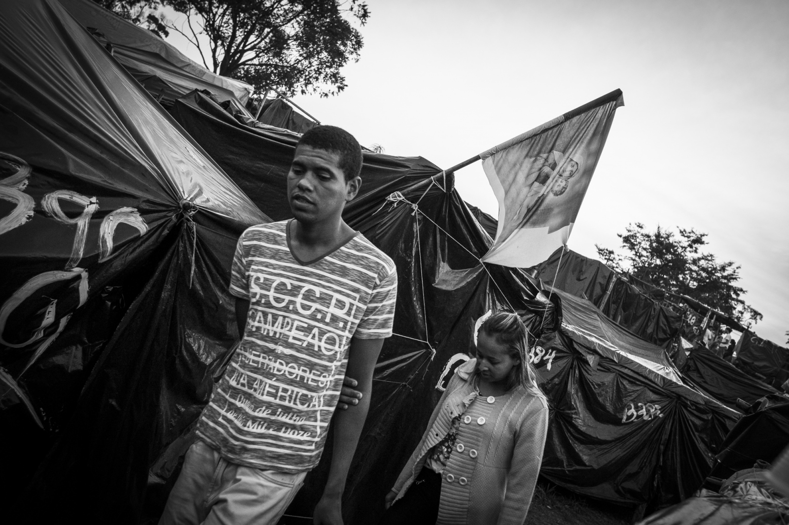 People living in  Copa do Povo (People's Cup) Camp pass in front of a shack with a flag with Jesus and Maria. Even after all adversity people didn't lost their faith. The Copa do Povo Camp, is just a few miles from the Arena Corinthians and has 5,000 homeless workers and their families occupied area of fifteen acres. They are homeless after rents skyrocketed because of the World Cup.