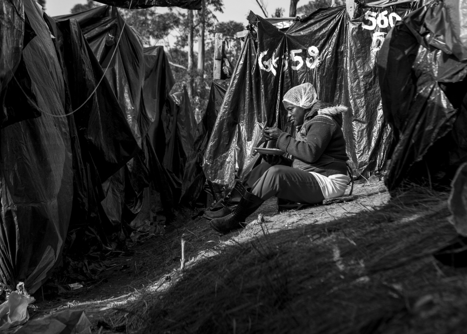 A woman eats between the shacks made of wooden sticks and black plastic bags on the Copa do Povo (People's Cup) camp, Itaquare, São Paulo. The Copa do Povo Camp, is just a few miles from the Arena Corinthians and has 5,000 homeless workers and their families occupied area of fifteen acres. They are homeless after rents skyrocketed because of the World Cup.
