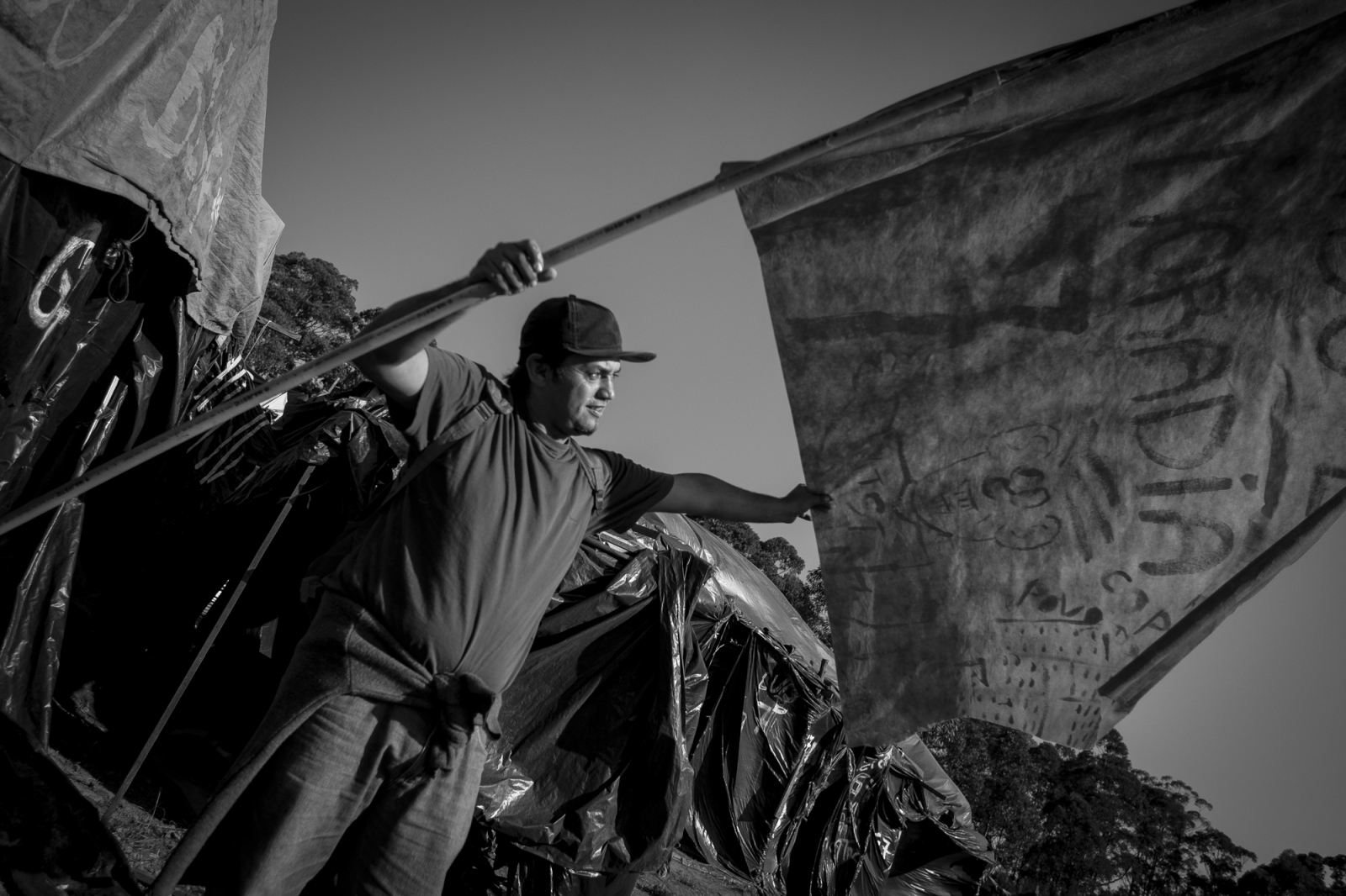 A member of the Movement of Workers Without Ceiling (MTST) prepares a flag for the protest demanding for housing not only for the residents of Copa do Povo but also for other camps around the city of São Paulo. The Copa do Povo Camp, is just a few miles from the Arena Corinthians and has 5,000 homeless workers and their families occupied area of fifteen acres. They are homeless after rents skyrocketed because of the World Cup.