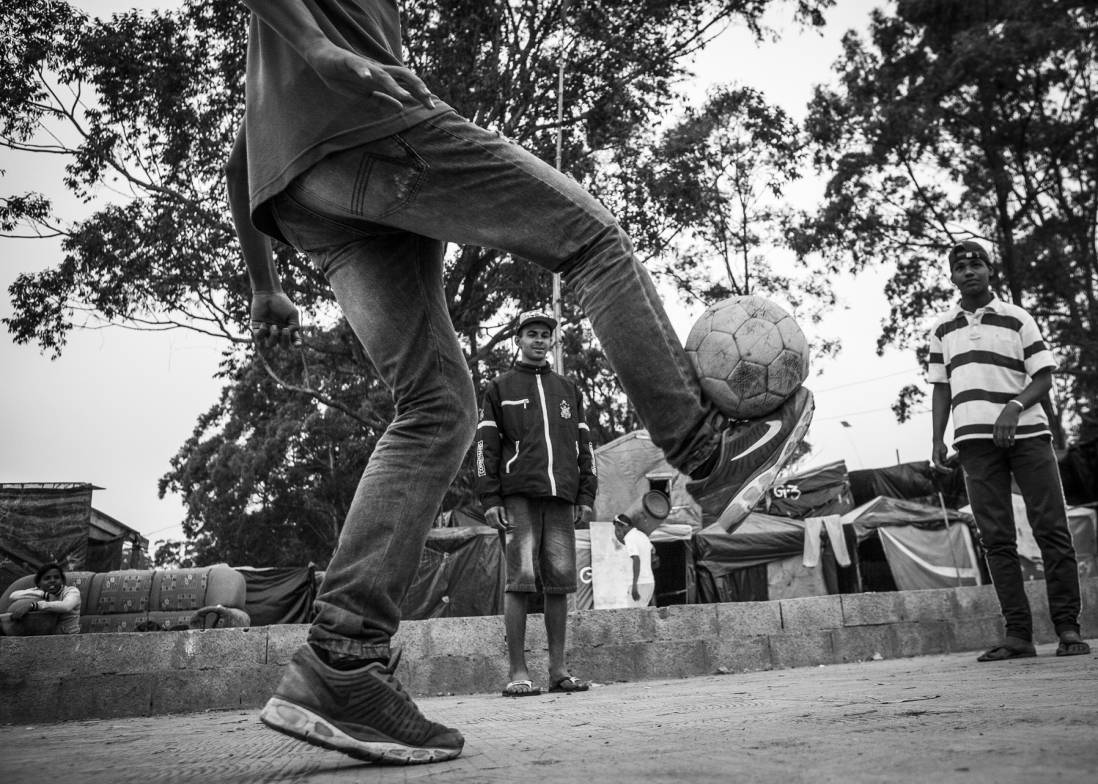 Ceará Machado plays football with his friends in front of the Copa do Povo (People's Cup) Camp in Itaquera, São Paulo. Even if the World Cup is the main reason to be without a roof he still loves the game and will suppport Brazil to lift the cup. The Copa do Povo Camp, is just a few miles from the Arena Corinthians and has 5,000 homeless workers and their families occupied area of fifteen acres. They are homeless after rents skyrocketed because of the World Cup.