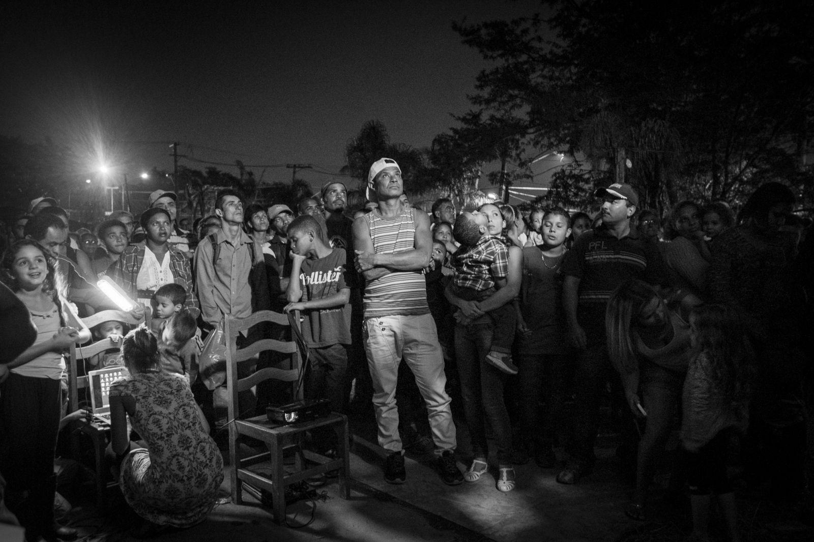 Habitants of Copa do Povo (People's Cup) Camp, Itaquera, São Paulo, listen to the leaders of the Movement of Workers Without Ceiling (MTST)  while they explain the negociations with the Brazilian Government. Every night they gather for debates and to coordinate the efforts to run the camp. The Copa do Povo Camp, is just a few miles from the Arena Corinthians and has 5,000 homeless workers and their families occupied area of fifteen acres. They are homeless after rents skyrocketed because of the World Cup.