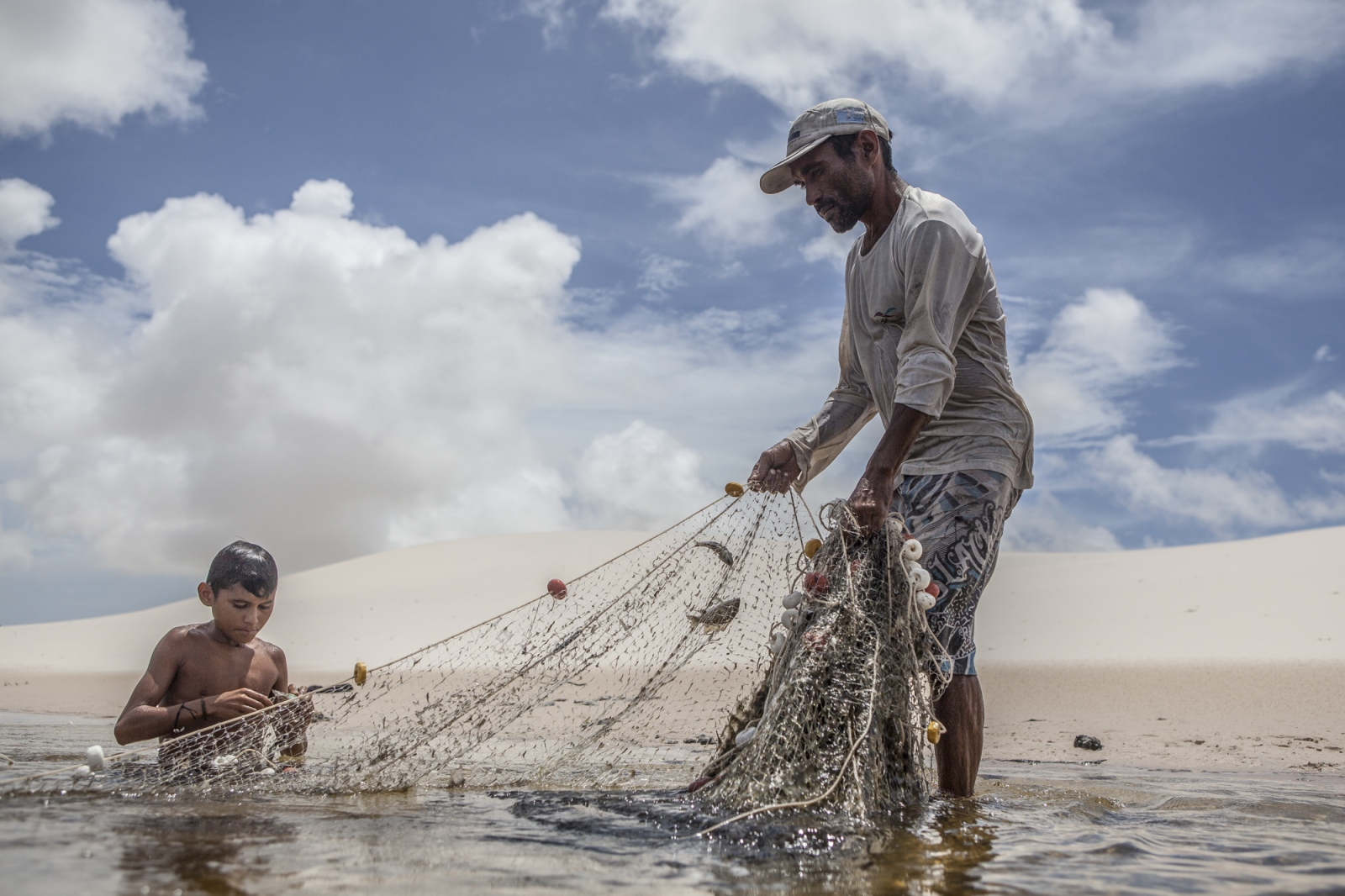 Aldemir Brito, 39, fishing with his son Adriel, 13, in one of the lagoons close to his house in Queimada dos Britos. The knowledge of living in the dunes is passed from father to son for generations. They live of fishing in the sea, which is two hours away. In the winter they breed fish on the lagoons, and cattle and goats that run free on the dunes. They have a small garden for farming but nothing major since they are afraid of the accelerating advance of the dunes that have already covered several houses.