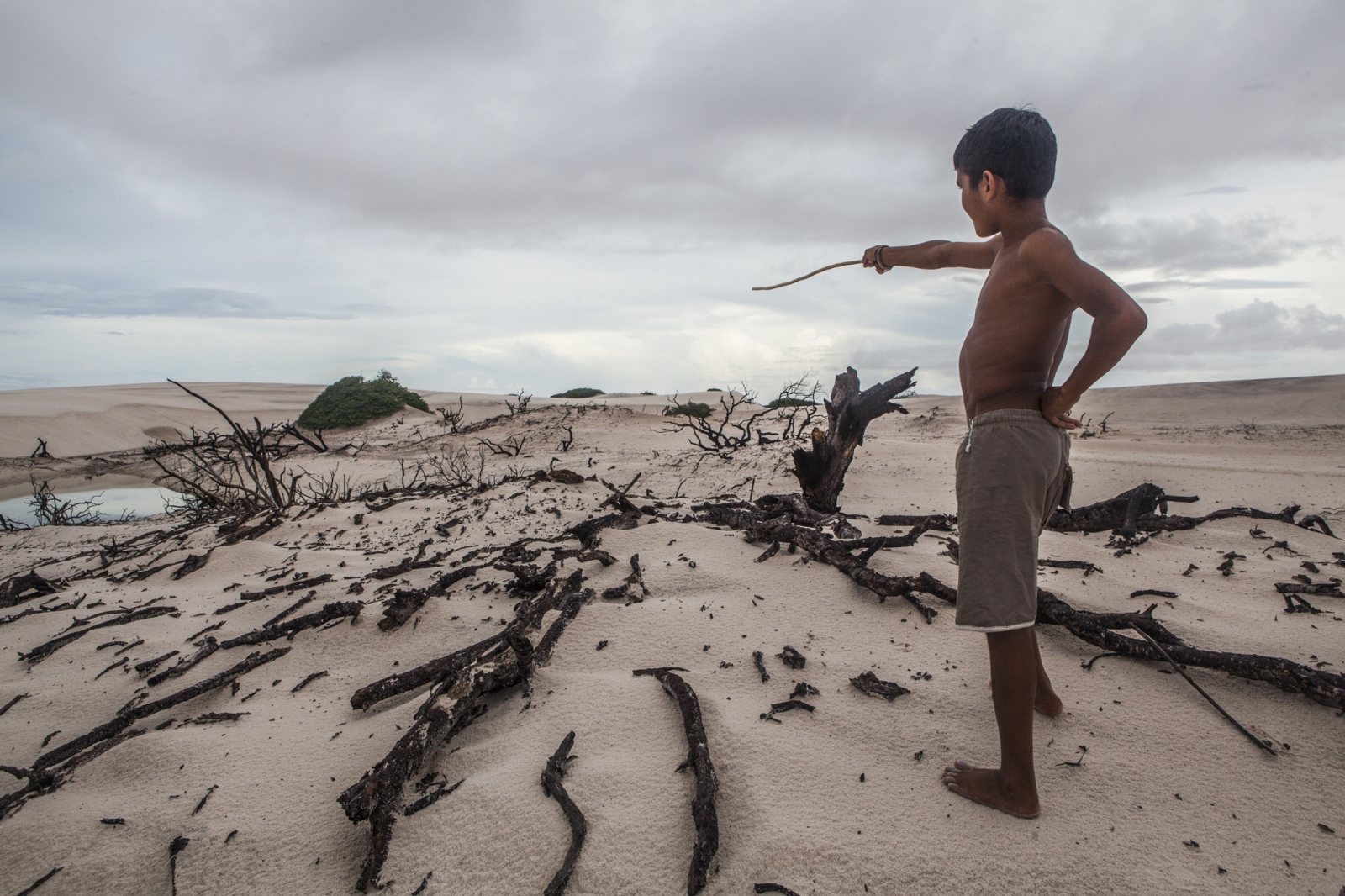 Adriel Brito, 13, points to the place where once was the house of his uncle. After he lost the house for the dunes he decided to move to the nearby city of Santo Amaro. During the summer, the lack of water and the strong winds make the dunes advance and take over parts of the oasis. But not only their life is threaten by the tourism and the sand. The Brazilian Institute of the Environment and Natural Resources (IBAMA) is planning to remove them since they live in a National Park.