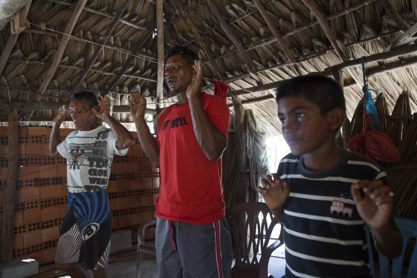 Eduardo, Zé Brito and  Manuel Brito during the mass in the community shack of the village. Every weekend a few members of the community get together for the Sunday prayer.