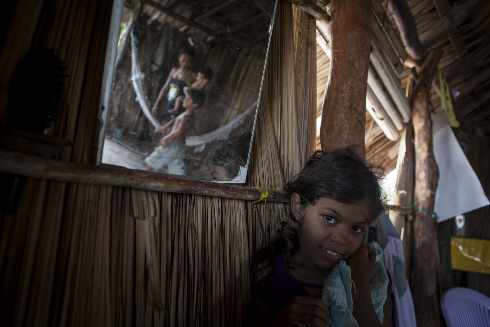 Rosa Brito, 7, in her house with her family. During the afternoons the children are free to walk around the oasis and the dunes and adults tend to visit each other's houses and socialize.