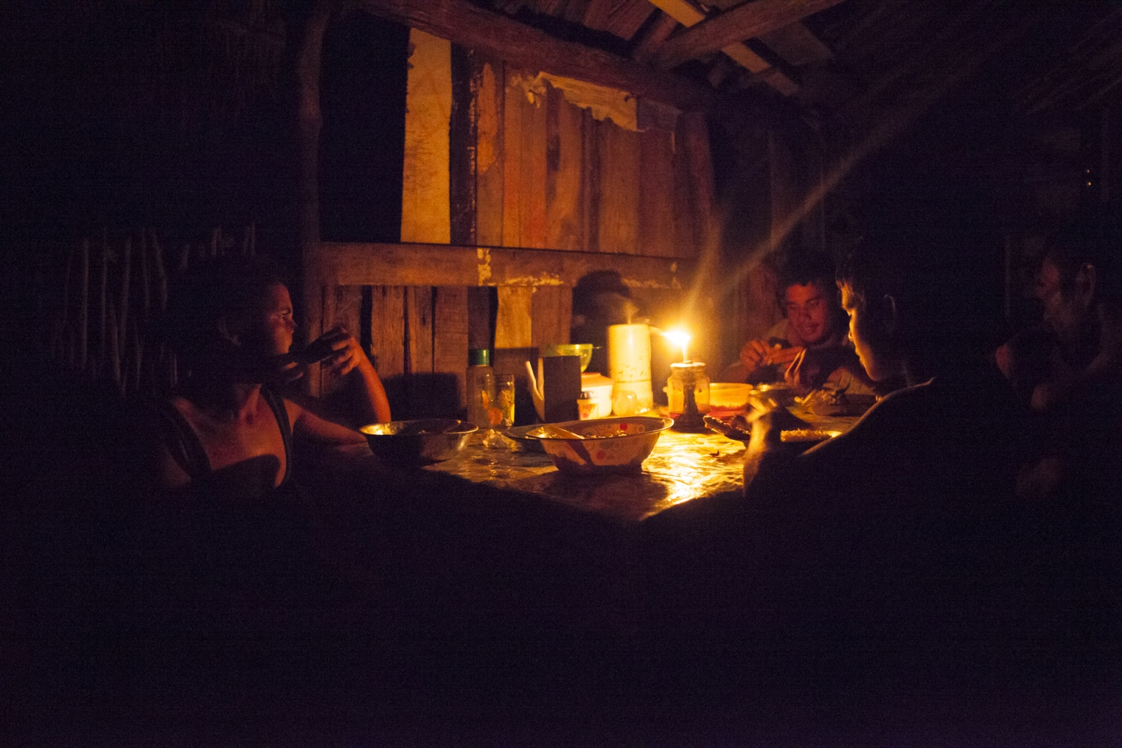 Auriela Brito has dinner with her sons, Tico and Adriel Brito. Electricity doesn't reach the Queimada dos Britos, so during the evening people relax and eat around kerosene lamps.