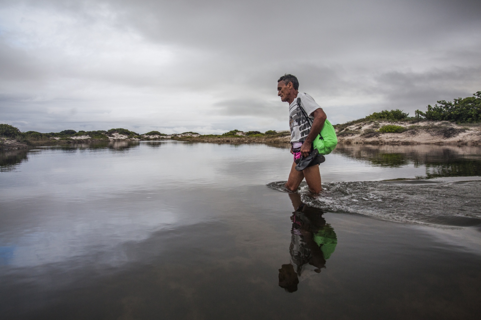 Eduardo, one of the  temporary residents that comes and goes from Queimada dos Britos, crosses a lagoon during his 4 hours walk to the closest village of Sucuruju. He is going to pick-up medicine from a friend of the Brito's family.