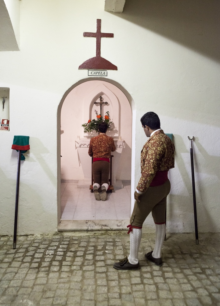 Guga Oliveira, one of the members of the group of Forcados of Évora, looks to another member of the group while he prays before the bullfight. Forcados are extremely  religious.