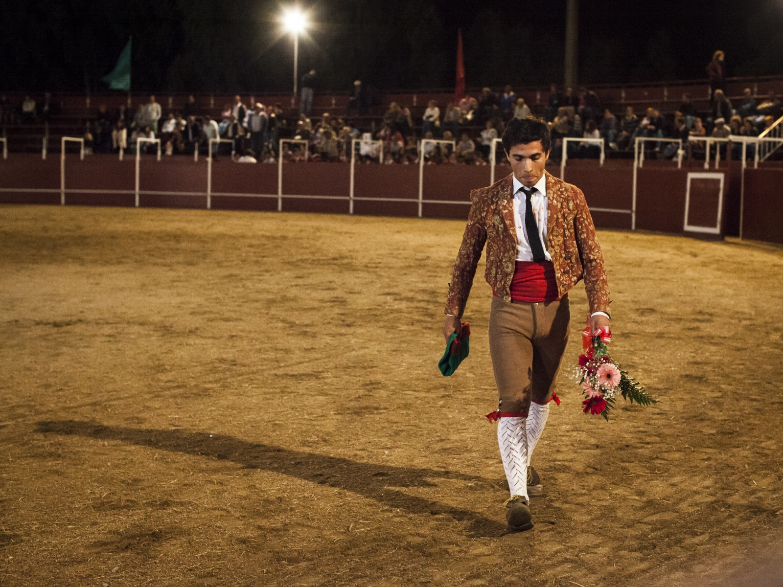Dinis Caeiro, a member of the Forcados of Évora, leaves the arena after a successful face catch. When the pega is done at the first attempt and with style, the forcado goes around the arena to receive applauses and flowers from the public.