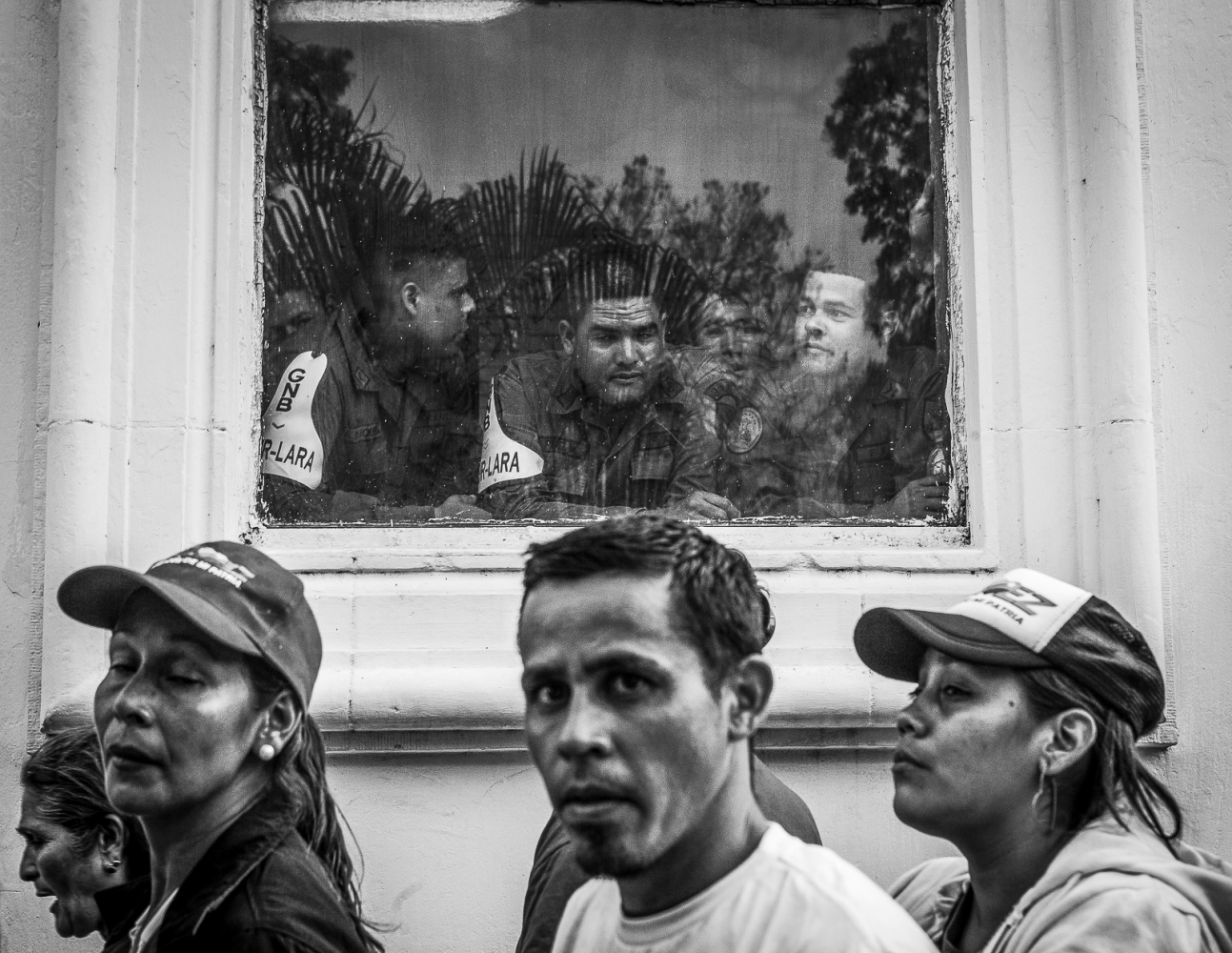 Members of the Bolivarian National Guard look through the window in the Military Academy, to the people outside queuing to see the remains of Venezuela's President, Hugo Chávez, during the funeral in Caracas, 8th March 2013